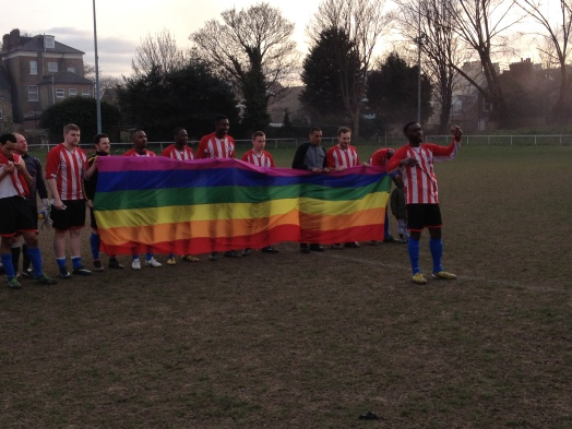 Clapton FC players holding a LGBT Rights flag at the game with Basildon. Photo by Kevin Blowe.